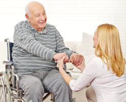 Elderly man in wheelchair with female staff