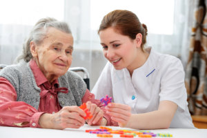 Elder woman and female staff playing puzzle